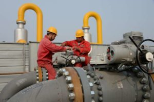Sinopec employees work on pipelines connecting a Sinopec natural gas facility and Binhai transmission station of China National Petroleum Corporation's (CNPC) Dagang oilfield, ahead of the winter heating season in Tianjin, China October 22, 2018. Picture taken October 22, 2018. REUTERS/Stringer  ATTENTION EDITORS - THIS IMAGE WAS PROVIDED BY A THIRD PARTY. CHINA OUT. - RC15837C5B70